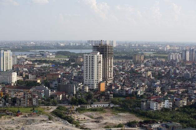 Residential properties stand near a construction site in Hanoi.  Photo credit: Bloomberg