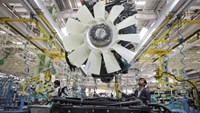 An employee lowers an engine onto a chassis on the assembly line at a truck factory in India. Photo credit: Bloomberg
