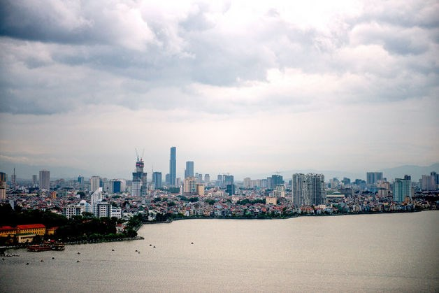 Residential and commercial buildings stand along the waterfront in Hanoi. Photo credit: Bloomberg
