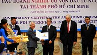 Le Hoang Quan (3rd L), chairman of the HCMC People's Committee, hands investment licenses to foreign investors in the city on June 21, 2014. Photo credit: Tuoi Tre