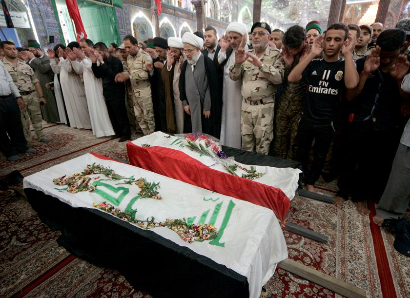 Mourners pray in front of the coffins of Shi'ite volunteers, who had joined the Iraqi Army and were killed during clashes with militants of the Islamic State, formerly known as the Islamic State of Iraq and the Levant (ISIL), during a funeral in Kerbala,