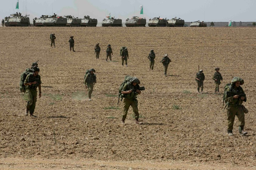 Israeli soldiers from the Nahal Infantry Brigade walk across a field near central Gaza Strip July 12, 2014. Photo credit: Reuters