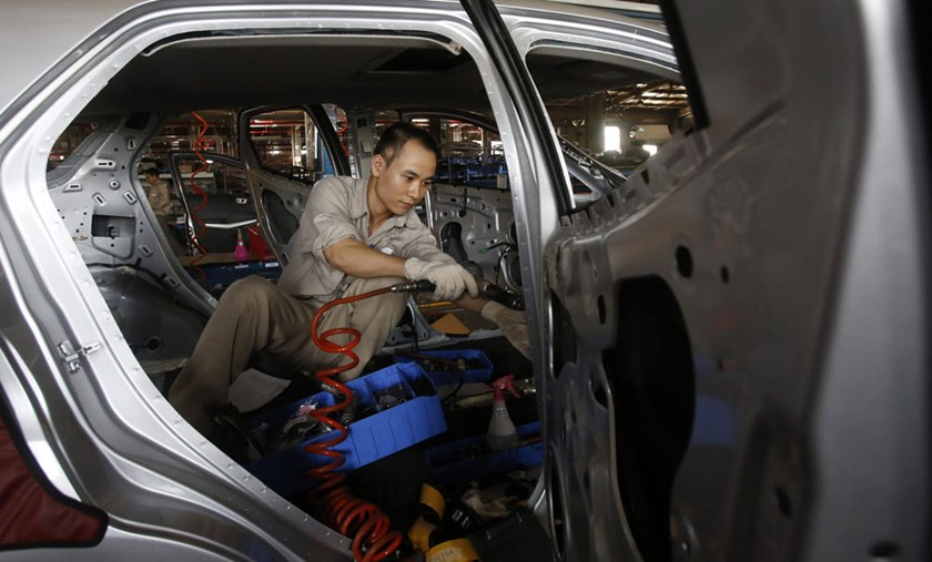 A man works on a vehicle at an automaker factory in Vietnam's northern Hai Duong province, outside Hanoi. Weak management and cumbersome administrative procedures have hampered Vietnam's competitiveness, experts say. Photo credit: Reuters