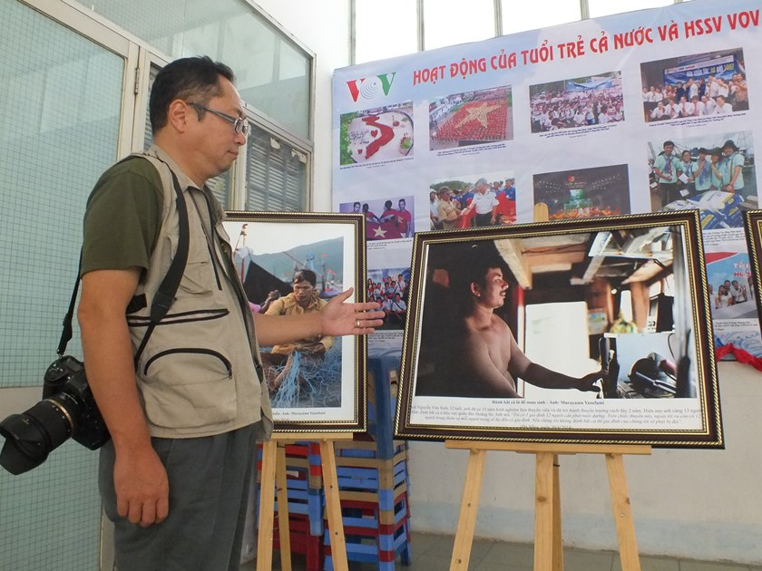 Murayama Yasufumi introduces a photo at his exhibition in HCMC. The photo shows a fisherman sailing his boat to the sea off the Paracels on June 30 in spite of threats from the Chinese vessels.