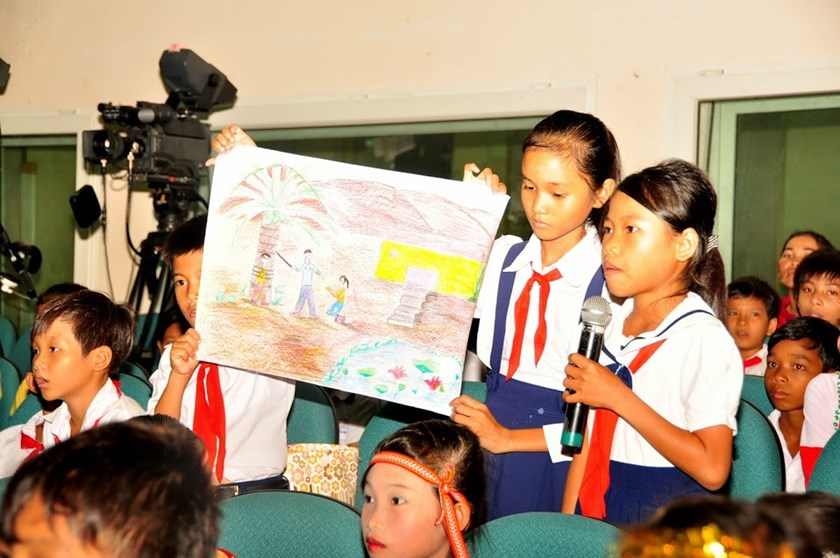 A schoolgirl speaks while her two classmates hold up a picture to illustrate her concerns about domestic violence directed toward children at a forum in Ninh Thuan Province on July 31. Photo credit: Oxfam