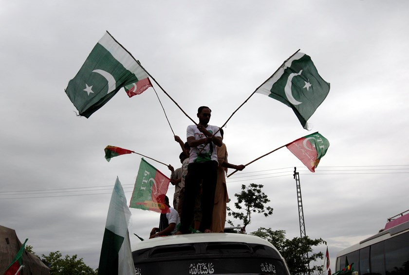 Supporters of Pakistan Tehreek-e-Insaf, a political party led by cricketer-turned-opposition politician Imran Khan, wave flags from the roof of a van as they arrive with the Freedom March in Islamabad August 16, 2014. More than 20,000 anti-government prot