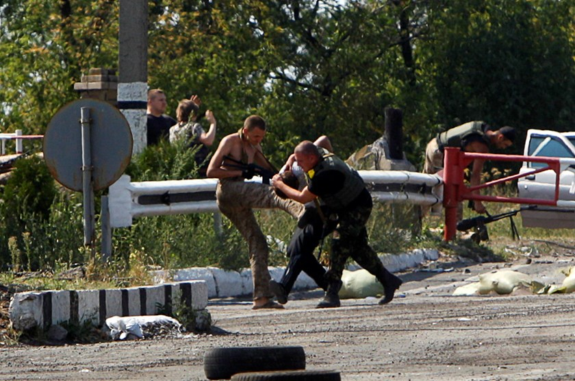 Ukrainian servicemen detain a pro-Russian activist at a checkpoint near the eastern Ukrainian town of Debaltseve, August 16, 2014. Ukrainian forces and pro-Russian separatists fought skirmishes near the Russian border on Saturday but there was no sign of