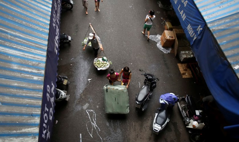 A fruit vendor walks behind women pushing a cart full of fabric in the Dong Xuan wholesale market in Hanoi. The government expects consumer prices to grow by 5 percent this year. Photo credit: Reuters