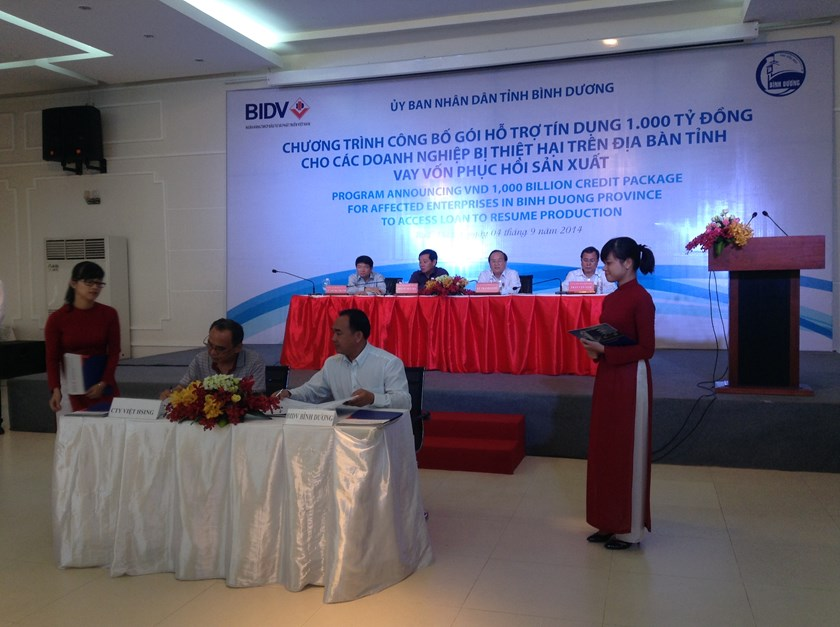 A representative of Taiwanese-owned Viet Hsing garment company (L) signs a loan contract with BIDV's Binh Duong branch on August 4, 2014. Photo credit: BIDV