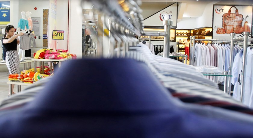 A woman checks a shirt inside a Vinatex supermarket in Hanoi September 15, 2014. The company on Monday raised US$57.3 million from the sale of 110.6 million shares at an auction organized by the HCMC Stock Exchange. Photo: Reuters