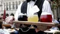 A waiter with a flight of Belgian beer featuring the colors of the national flag in Brussels. Photo: Reuters