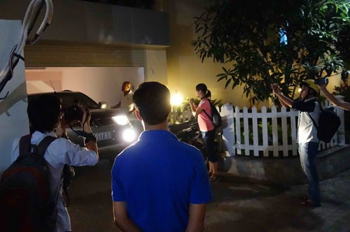 Reporters take photos of a police car leaving the headquarters of VN Pharma after searching the firm and collecting a number of documents.
