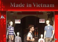 A tourist walks past a clothing shop in Hanoi on October 3, 2014. Inventory and tax debts in Vietnam are up from last year. Photo: Reuters