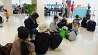 Passengers sit on the floor at HCMC's Tan Son Nhat airport on September 4, 2014. Their flight was delayed but there were not enough seats for them. Photo: Bach Duong