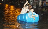 Two young men manage to go through a flooded street in Da Nang City October 25, 2014. Photo: Nguyen Tu