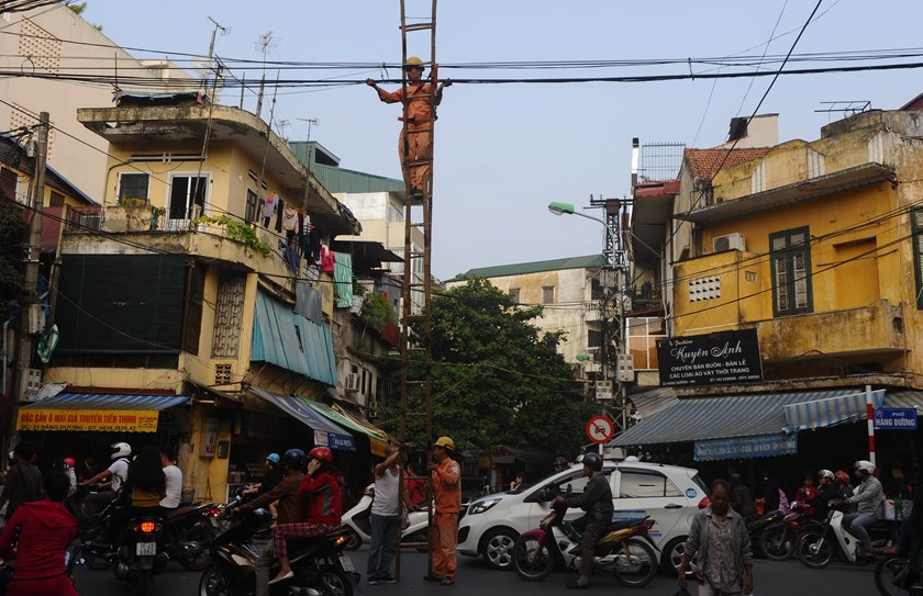 Electricity workers use a long bamboo ladder to fix an electrical cable in downtown Hanoi on November 20, 2014.  Photo credit: AFP