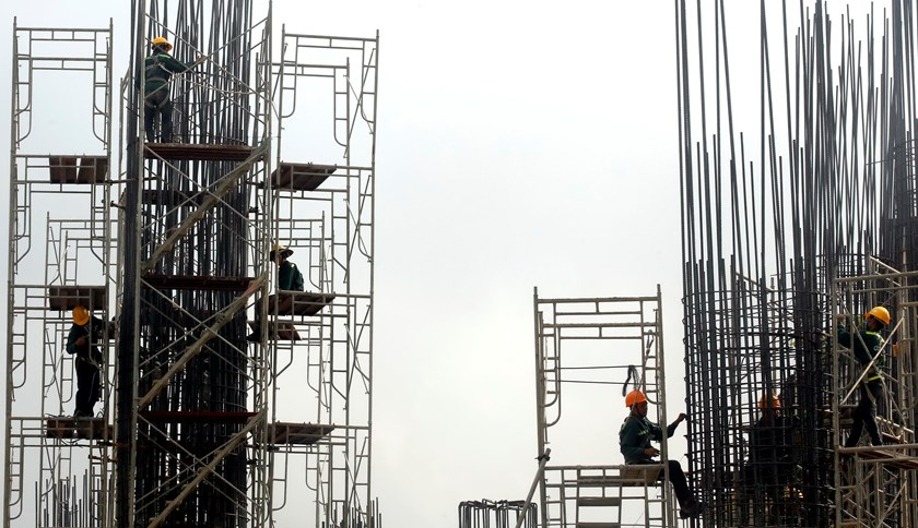 Laborers arrange steel structures at the site of a future office building in Hanoi. Photo credit: Reuters