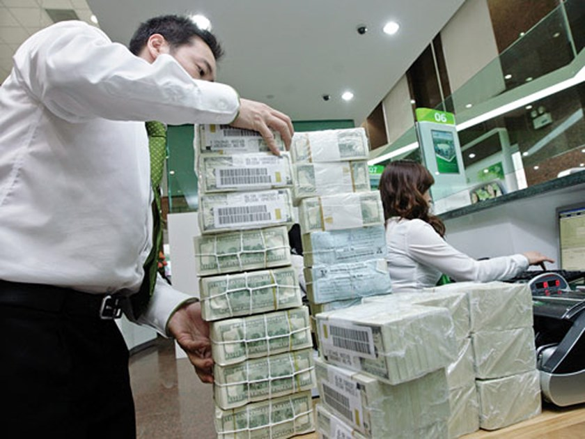 A bank employee stacks bundles of dollar notes at a bank in Hanoi. Photo: Ngoc Thang