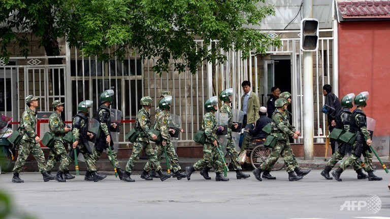 Fully armed Chinese paramilitary police patrol a street in Urumqi, the capital of China's Muslim Uighur homeland of Xinjiang, on May 23, 2014. Photo credit: AFP