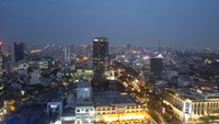 Commercial and residential buildings stand illuminated at night in Ho Chi Minh City. Photo credit: Bloomberg