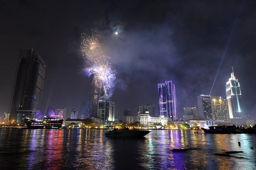 Fireworks are seen displayed from Bitexco tower, the tallest building of Ho Chi Minh City, for the New Year celebrations from the other bank of Saigon River on January 1, 2015. Photo credit: AFP