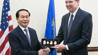 Minister of Public Security Tran Dai Quang (L) shakes hands with Director of the Federal Bureau of Investigation (FBI) James Comey in Washington on March 16, 2015. Photo credit: CAND
