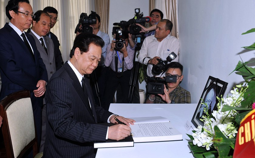 Vietnam's Prime Minister Nguyen Tan Dung (C) writes down a message of condolences in front of a portrait of Singapore's late former leader Lee Kuan Yew at the Singaporean embassy in Hanoi on March 23, 2015. Photo credit: AFP