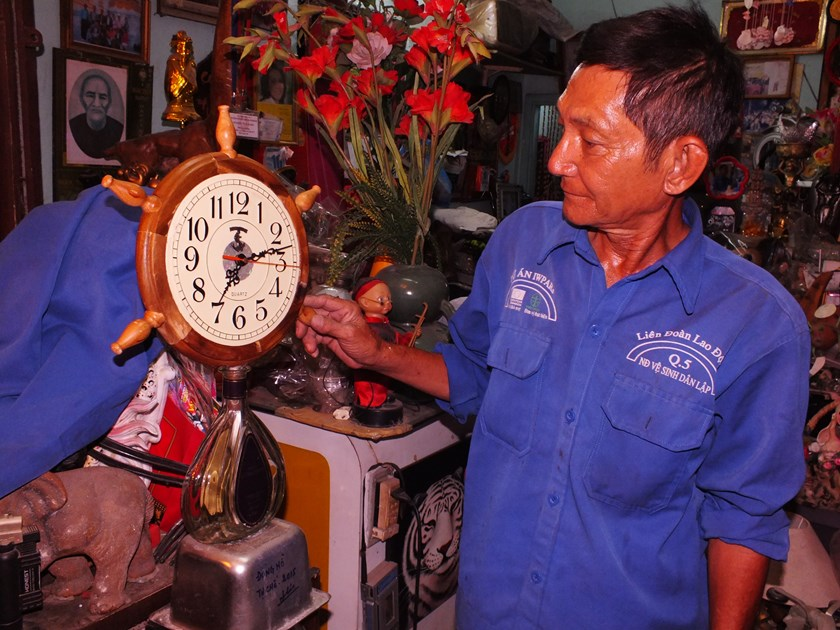 Tong Van Thom and a new clock he made from a broken clock, a wooden decorative item, a wine bottle, and a metal food container. Photo: Thao Vi