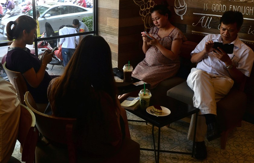 People use smartphones to check the Internet over wifi at a coffee shop in Hanoi. Photo credit: AFP