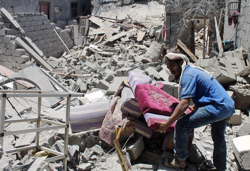 A Yemeni man searches for survivors under the rubble in houses destroyed by an overnight Saudi-led air strike on a residential area in the port city of Aden's Dar Saad suburb, on May 2, 2015. Photo: AFP