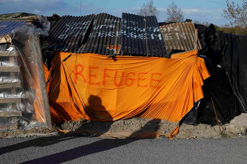 "Shadows from migrants are cast on a makeshift shelter with the written word ""Refugee"" in Calais, France, April 30, 2015. African migrants, principally from Eritrea and Sudan, gather in this northern French port city after they travelled from the Mediterra"