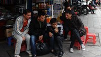 Men read news from a smartphone on a commercial street in downtown Hanoi. Photo: AFP