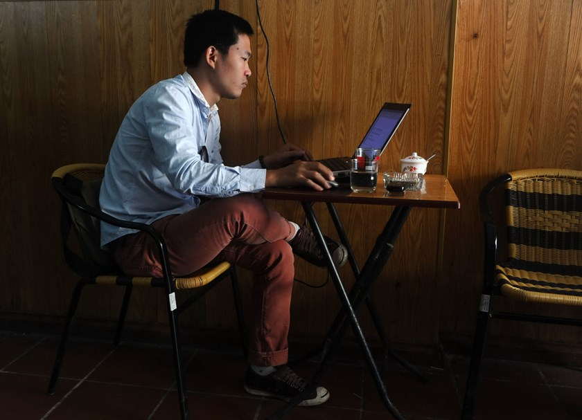 A man uses a laptop inside a coffee shop in downtown Hanoi. Photo: AFP