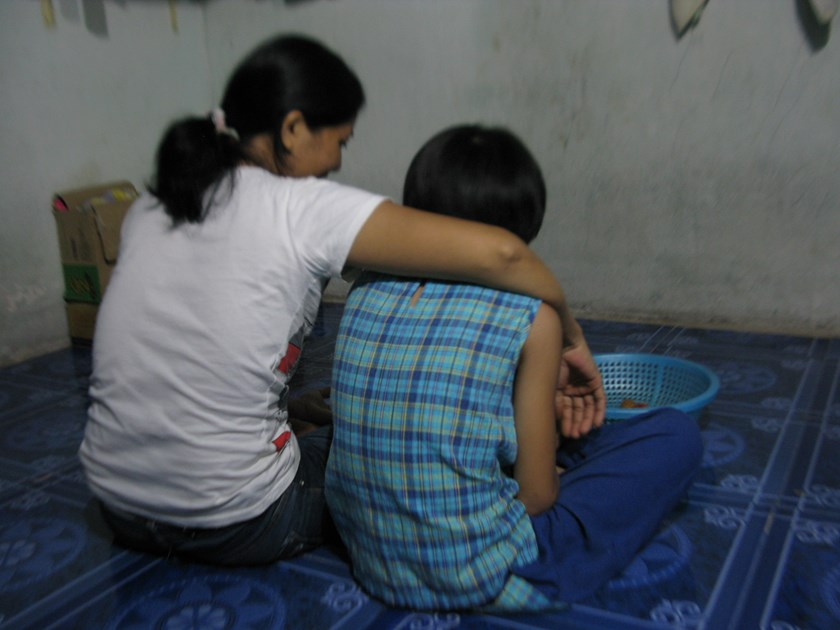 Duong Thi Hoa Ly (left) talks with her oldest daughter, Thanh, in their rented room in Ho Chi Minh City's Hoc Mon District on June 5, 2015. Thanh will soon return to a shelter in District 7 where she has lived since November . Photo: Thao Vi
