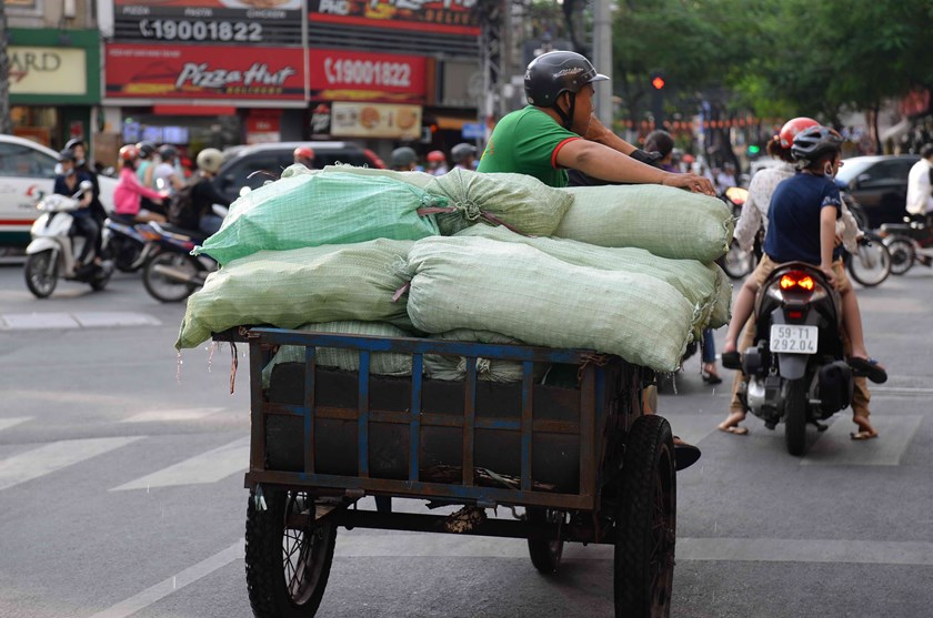A self-modified three-wheel vehicle is on the way to carry bags of ice cubes to restaurants and cafés in Ho Chi Minh City. Photo: Diep Duc Minh