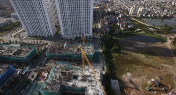 Apartment buildings under construction are seen near the old residential area of Vinh Tuy village in Hanoi July 1, 2015. Photo: Reuters