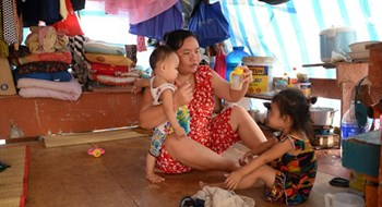 A woman takes care of her children in a makeshift tent near a construction site in Ho Chi Minh City's District 2 as her husband works as a hod carrier. Photo: Lam Ngoc