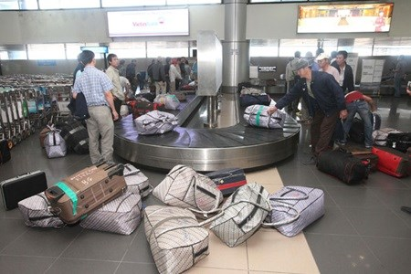 Passengers pick up their luggage at the Noi Bai International Airport in Ha Noi. Photo credit: VNA