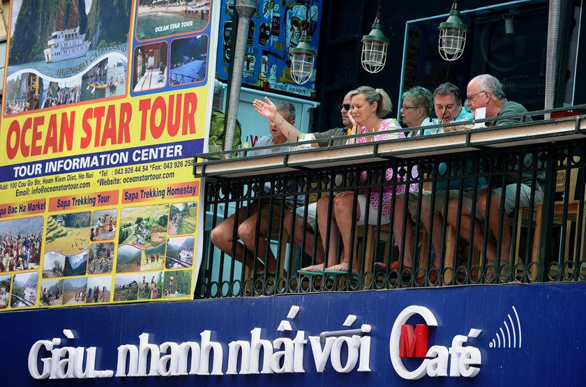 Foreign tourists sit at the terrace of a bar overlooking a road in the old quarter of Hanoi.  Photo: AFP