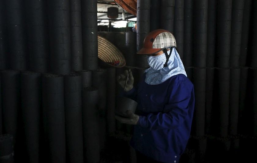 A woman works at a coal factory outside Hanoi. Photo: Kham/Reuters