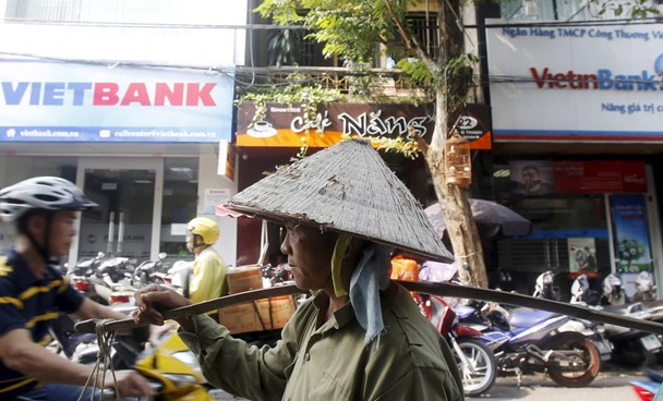 A fruit vendor walks past branches of Vietbank and VietinBank in Hanoi on October 22, 2015. Photo: Kham/Reuters
