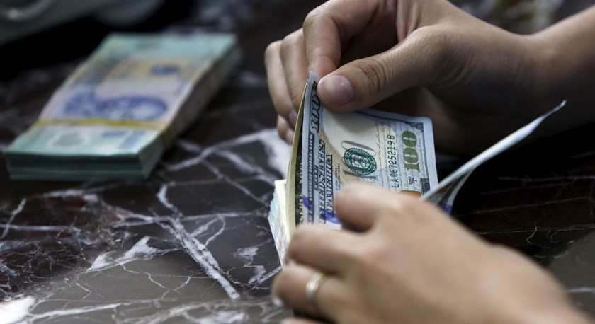 An employee counts US dollar bank-notes near Vietnamese dong bank-notes at a bank in Hanoi on August 12, 2015.  Photo: Reuters/Kham