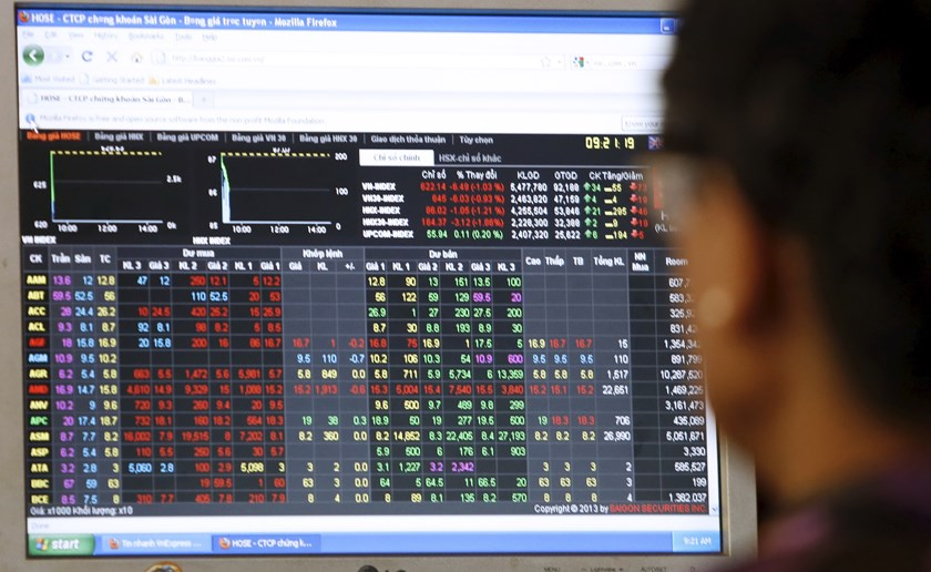 An investor looks at a stock market screen at a securities company. Photo: Kham/Reuters