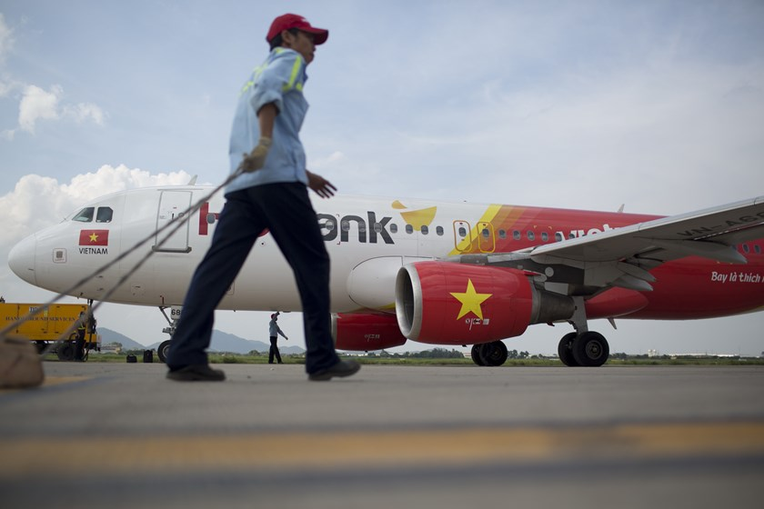 Employees work beside a VietJet Air aircraft on the tarmac at Noi Bai International Airport in Hanoi. Photo: Brent Lewin/Bloomberg