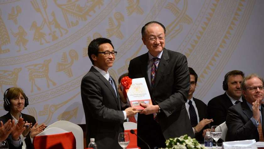 World Bank Group President Jim Yong Kim (centre R) and Vietnam's Deputy Prime Minister Vu Duc Dam (centre L) hold a copy of the Vietnam 2035 report during its launch ceremony in Hanoi on February 23, 2016. Photo: Hoang Dinh Nam/AFP