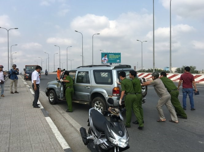 Police officers block a car on Nuoc Len Bridge in Binh Tan District after a 20-km chase. Photo: Duc Thanh/Tuoi Tre
