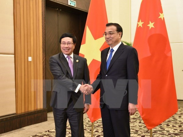 Vietnam's Deputy Prime Minister and Foreign Minister Pham Binh Minh (L) shakes hand with Chinese Premier Li Keqiang in China's Hainan province on March 23, 2016. Photo credit: VNA