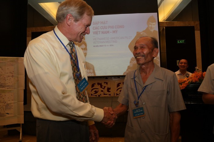 Veteran Nguyen Van Bay (R) shakes hands with a former American pilot at the meeting. Photo credit: Thanh Huyen/PetroTimes