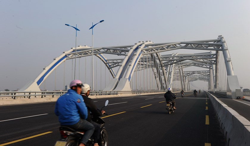 Motorcyclists ride on a bridge on a road linking Hanoi with northern Vietnamese provinces in the suburbs of Hanoi on January 15, 2015. Photo credit: Hoang Dinh Nam/AFP