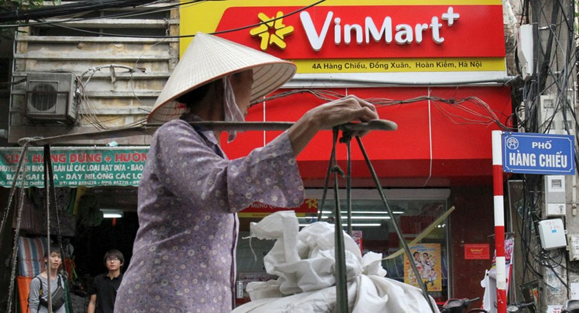 A woman walks past a VinMart+ store in Hanoi on October 12, 2015. Photo credit: Kham/Reuters
